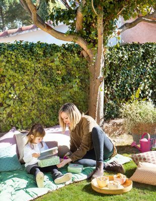 mujer y nina sentadas en cesped jardin 992x1280